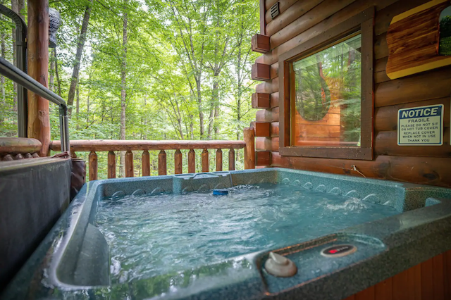Hot tub on cabin porch with view of trees