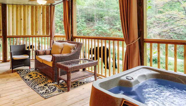 Cabin porch with hot tub and comfy furniture