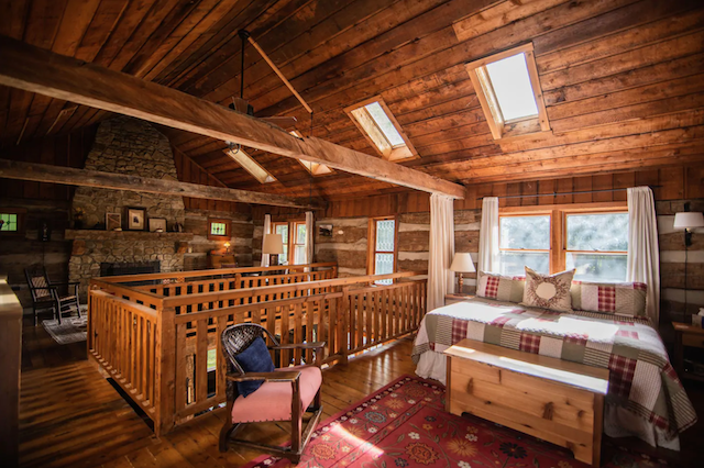 Covered Bridge Log Cabin upstairs bedroom with fireplace