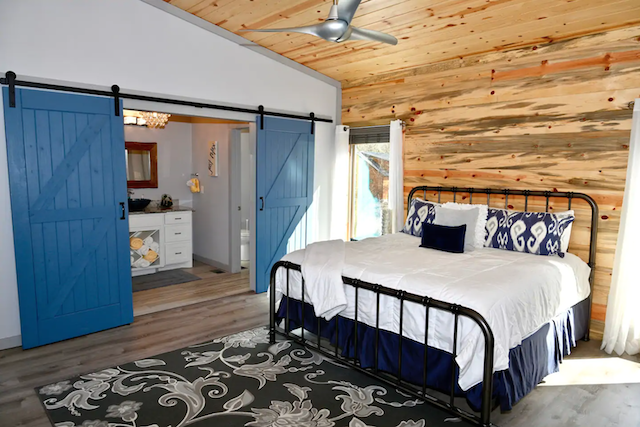 cabin bedroom with barn doors to bathroom