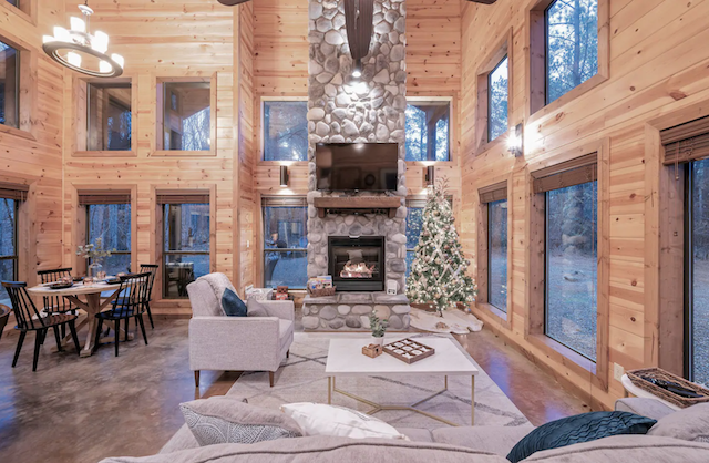 large open cabin living room with tops of windows and fireplace